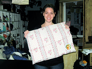 Rational Animal volunteer Michelle Aptman shows off a cage comforter stitched at a Mother's Comfort Project sewing event.