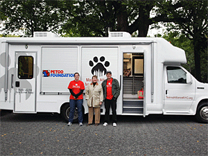 Mayor's Alliance staff members Siobhan Healy and Steve Gruber join President Jane Hoffman by the new adoption van at the Petco National Adoption Reunion in Central Park. (Photo by Jenna Leigh Teti)