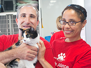Alliance volunteers, David Glicksman and Lydia Arroyo, introduced Madeline and other adoptable cats and dogs to Brooklyn Cyclones fans on the Alliance adoption van outside of MCU Park at Bark in the Park. (Photo by Joe Galka)