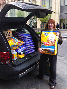 Volunteer Cathy Browne loads donated Pedigree dog food into her car to take to the Rockaways for distribution. (Photo by Evon Handras)